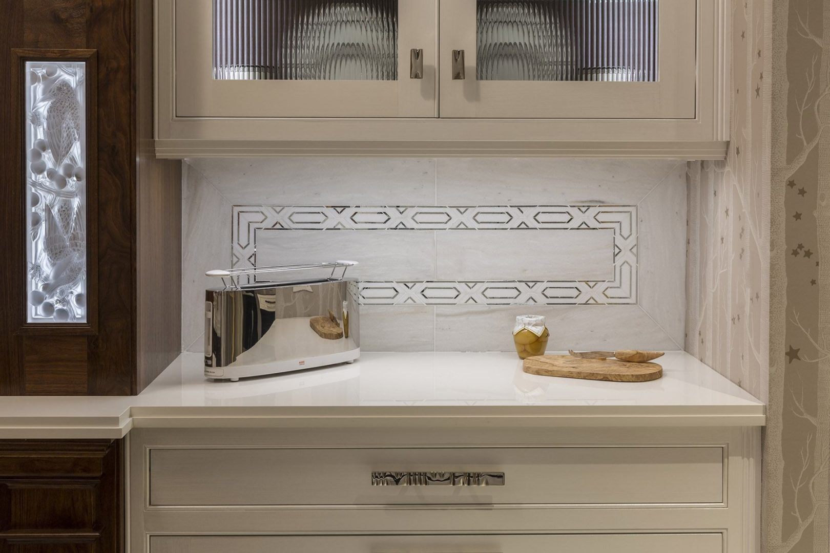 AKDO's White Haze marble and Allure radiance silver mirror border create sophisticated backsplash alongside warm wood cabinetry by Clive Christian and genuine Lalique crystal backlit inset panels.