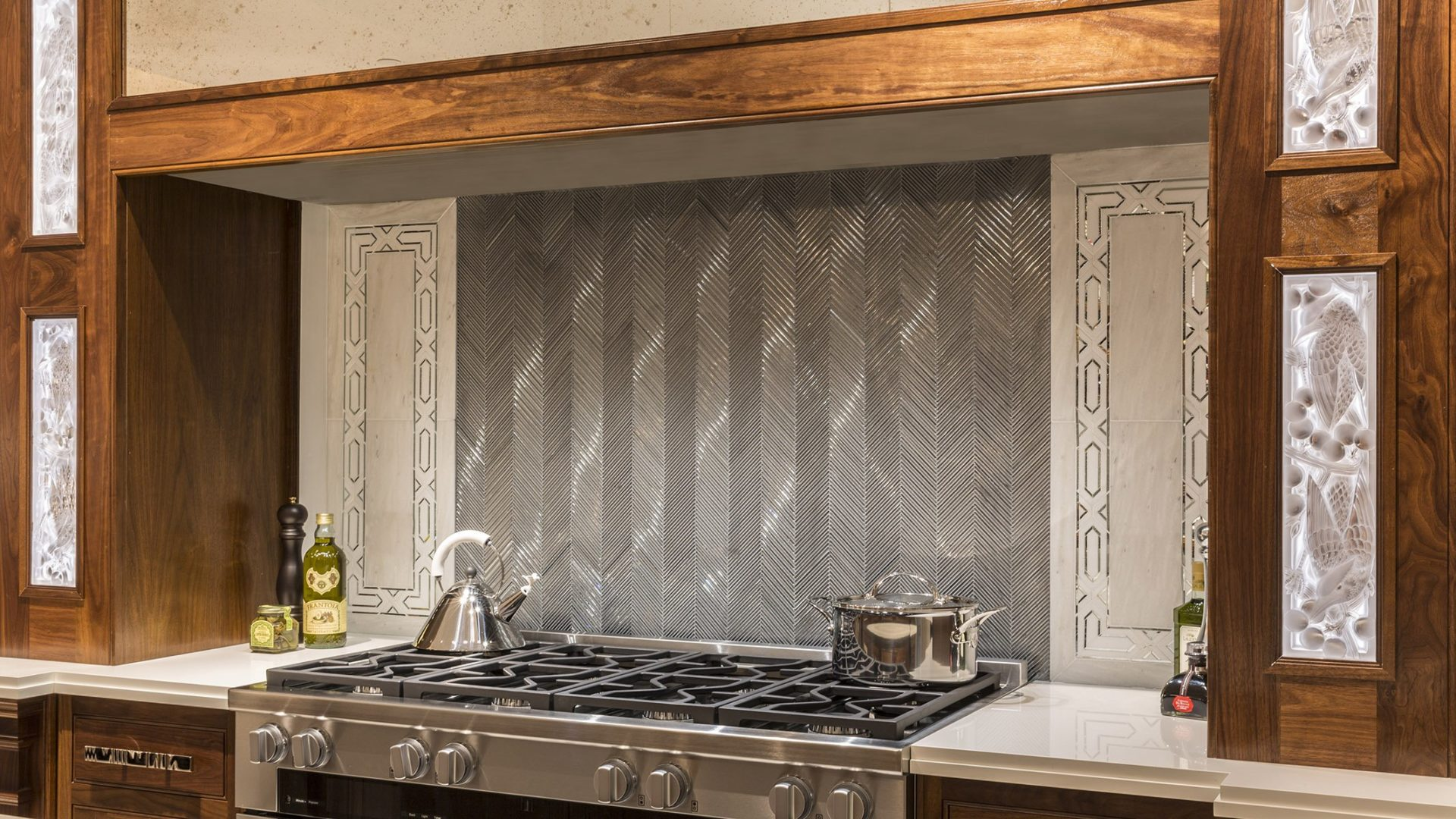 Textile Glass Mosaic in Silver Silk in the Ikat pattern creates a hearth effect. White Haze marble and an Allure radiance border complete the design.