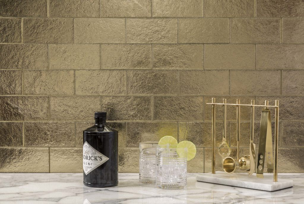 A bar that glitters in the matching Gold Silk subway tile.